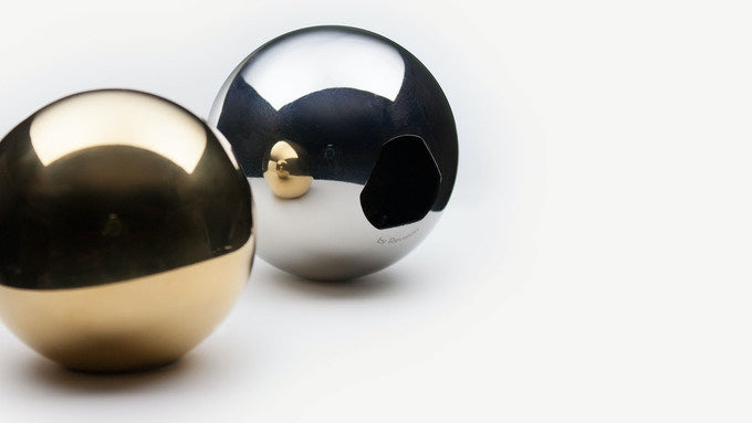 Two Convex bottle openers on a white bacground, one stainless steel and one gold.