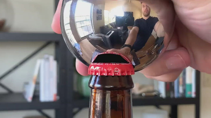 Revision Sainless Steel Convex Bottle Opener prying red cap off of bottle.