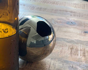 Revision Sainless Steel Convex Bottle Opener on wooden table behind brown bottle.