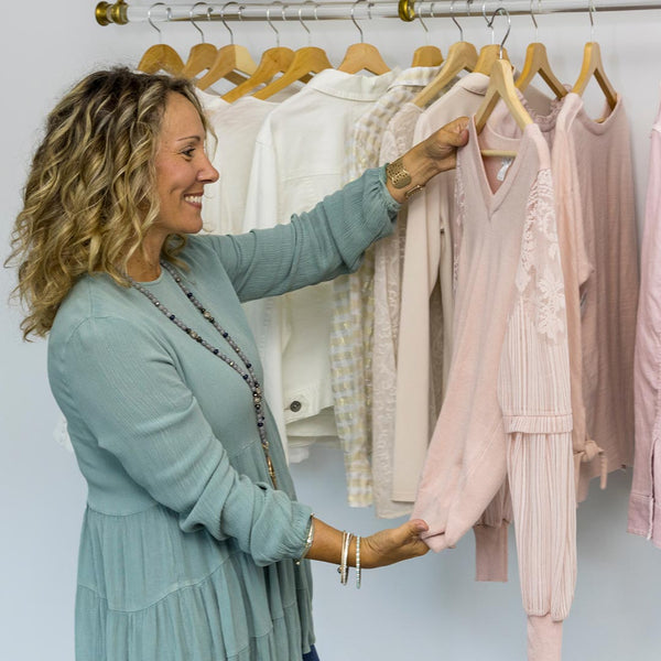 Women looking through her closet to sell her clothing for cash at Clothes Mentor