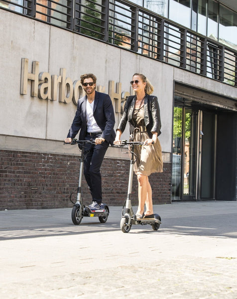 Couple riding Egret-Eight V2 adult electric scooters in street