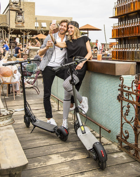 Couple at bar with Egret-Eight V2 adult electric scooters