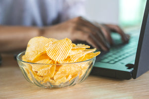 A bowl of potato chips sits on a desk with hands typing on a laptop in the background