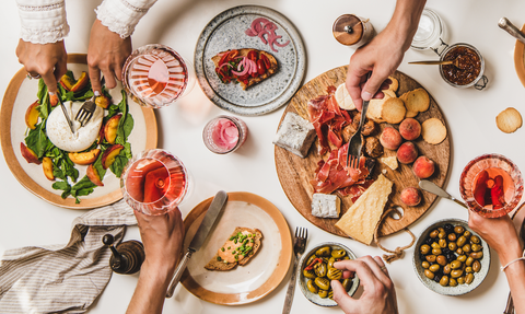 Peoples hands over a table with food and rosé pink wine