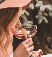 Girl sips rosé wine from a cocktail glass.
