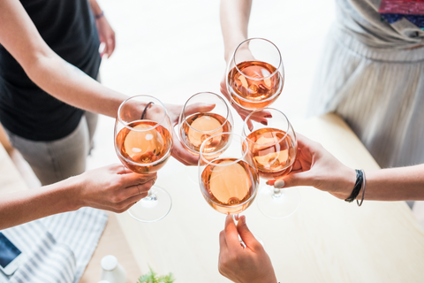 Group of friends clinking glasses of rosé wine