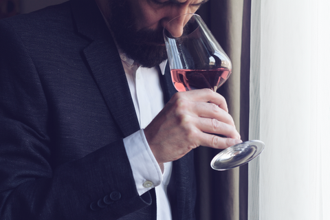 Suited man sniffing rosé wine
