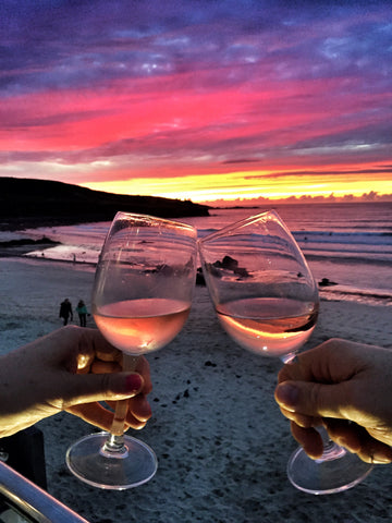 Two women clinking glasses of Rosé wine at a beach at sunset