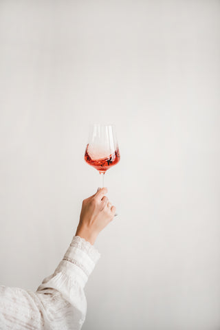Woman's hands holding a glass of rosé wine
