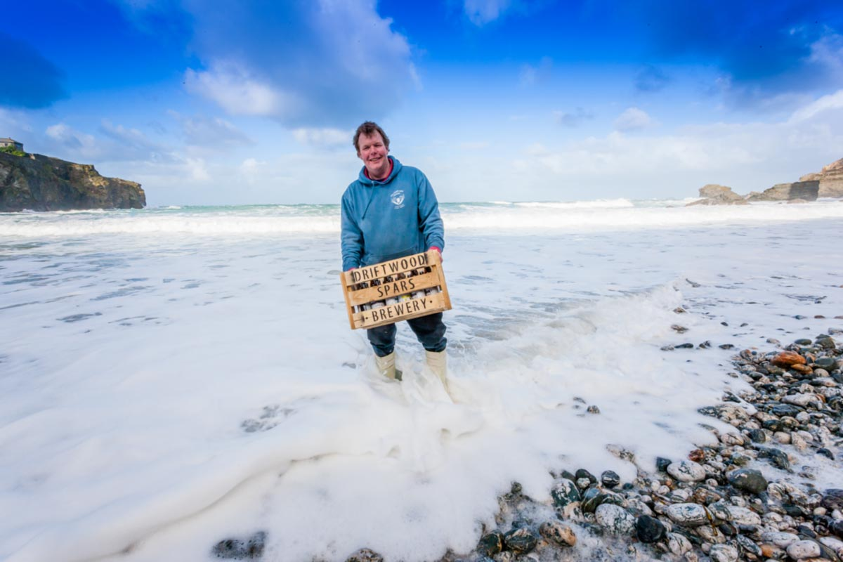 Pete the brewer in the sea at St Agnes Cornwall with a crate of beer