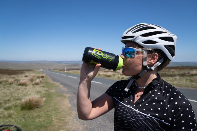 A female cyclists stood by the side of a road over a moorland drinking from a black and green Voom bottle
