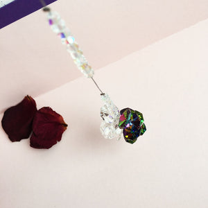 "The ""Best of Both Worlds"" suncatcher next to rose petals."