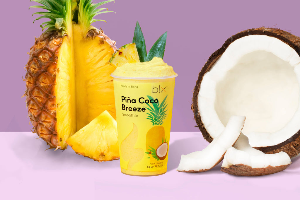 Pina Cocoa Breeze smoothie standing next to natural ingredients like coconut and pineapple