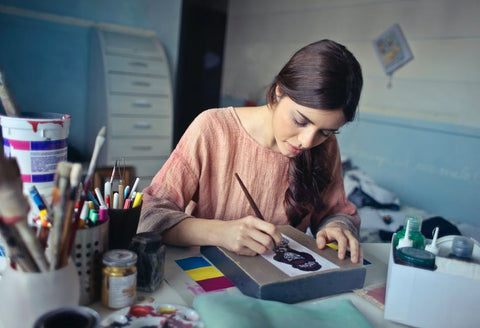 A woman sitting at her desk and painting
