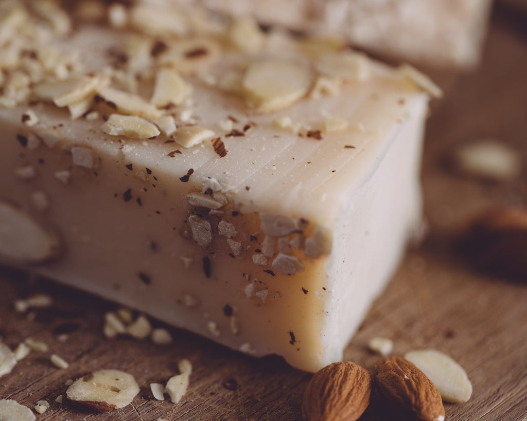 Close-up photographs of handmade organic almond cake bar soap.
