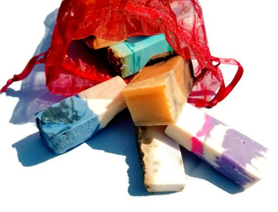 Assorted handcrafted soap pieces shown in red jewel toned bag.