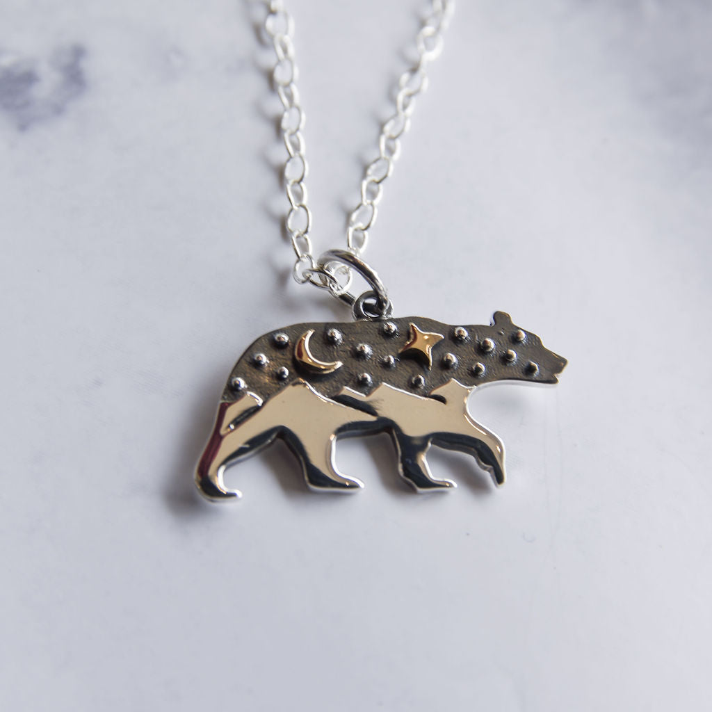 Sterling silver and bronze bear necklace with mountain and starry night scene.