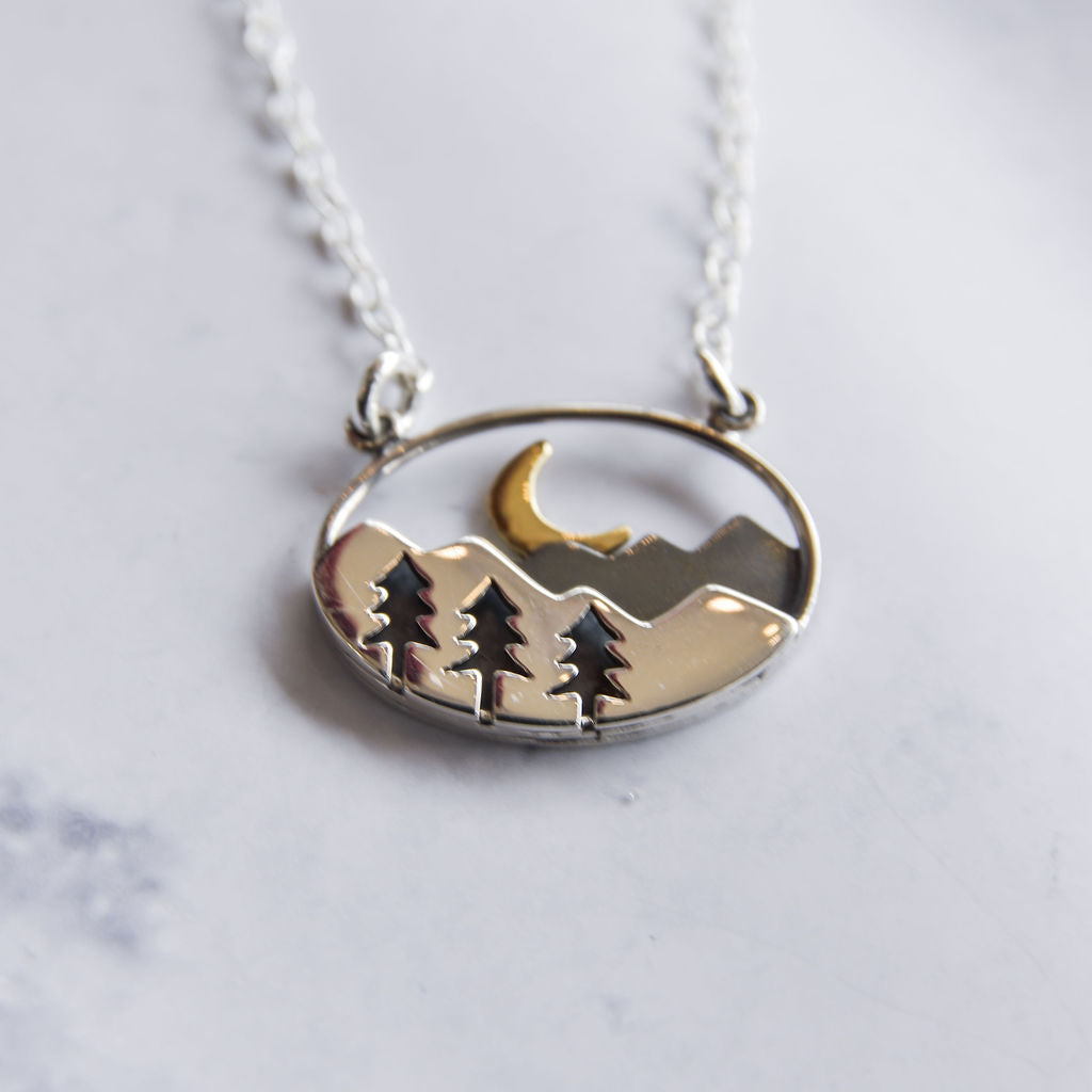 Sterling silver and bronze oval necklace with mountain, forest, and crescent moon.