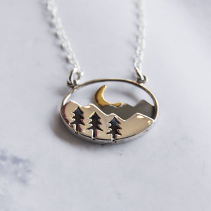 Close up of sterling silver and bronze oval necklace with mountain, forest, and crescent moon.