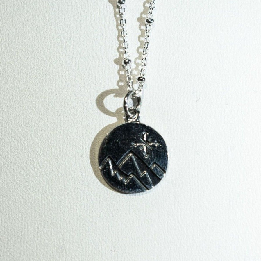 Sterling silver compass and mountain necklace.