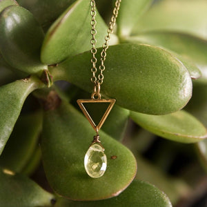 Brass triangle necklace with oval lemon quartz pendant below.