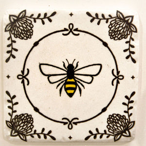 Bee coaster with a decorative circle and small bee.