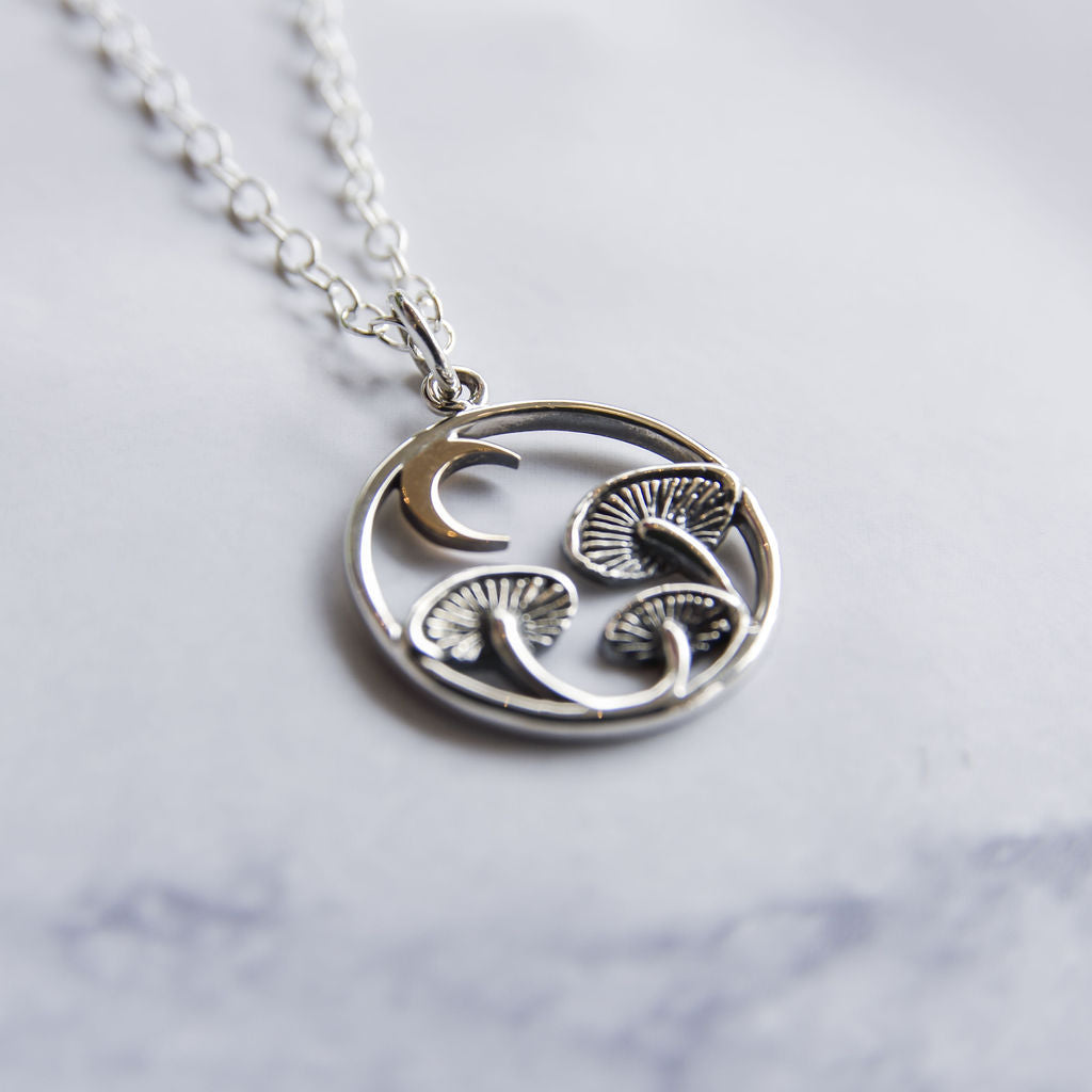 Sterling silver and bronze circular necklace with mushrooms and crescent moon.