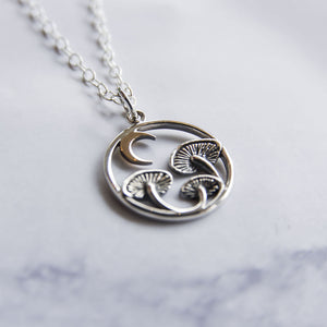 Close up of sterling silver and bronze circular necklace with mushrooms and crescent moon.