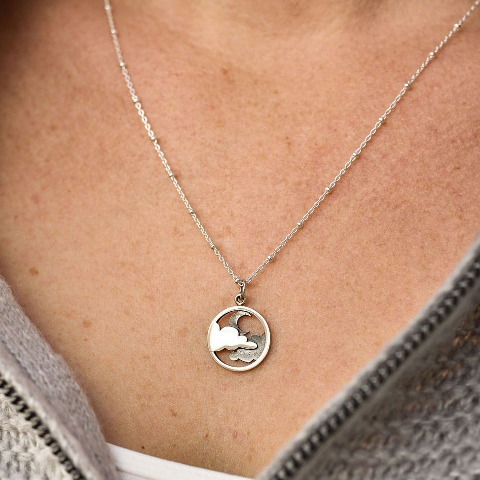 Sterling silver necklace with a circular pendant featuring a crescent moon covered by clouds.