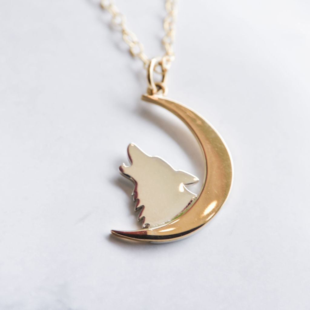 Sterling silver and bronze necklace of wolf howling at the moon.