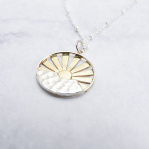 Close up of stunning sterling silver and bronze sunrise pendant.