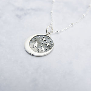 Close up of sterling silver circular pendant with snowy mountain peaks, starry sky, inside a crescent moon.