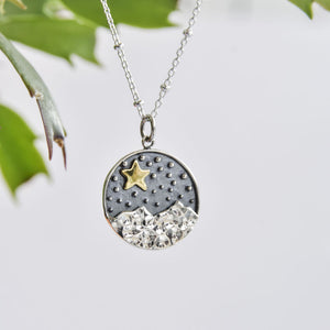 Sterling silver circular pendant with rugged mountains and bronze star.