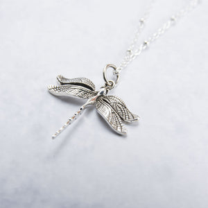 Close up of intricate sterling silver dragon fly necklace