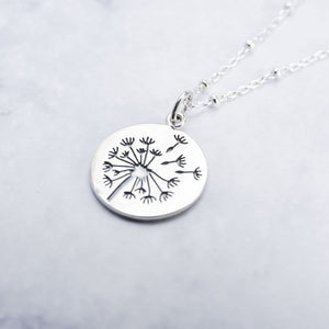 Close up of sterling silver circular pendant with pressed dandelion design.