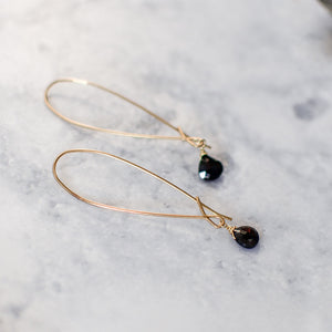 close up of black spinel drop earrings in brass