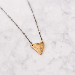 Triangle bronze pendant with cubic zirconia close up