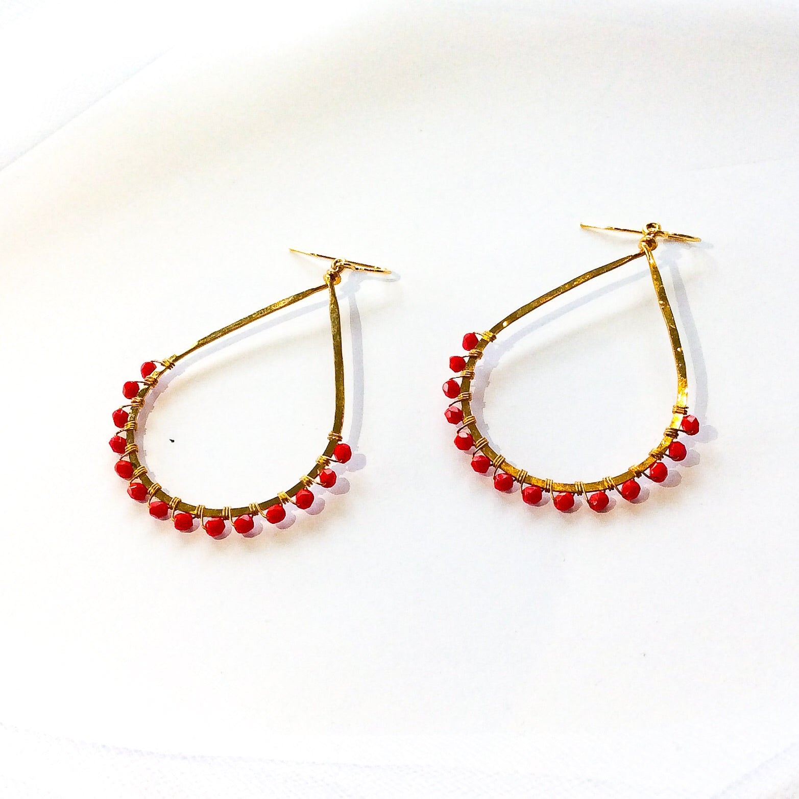 hammered gold plated tear drop earrings with red beads wired onto the end