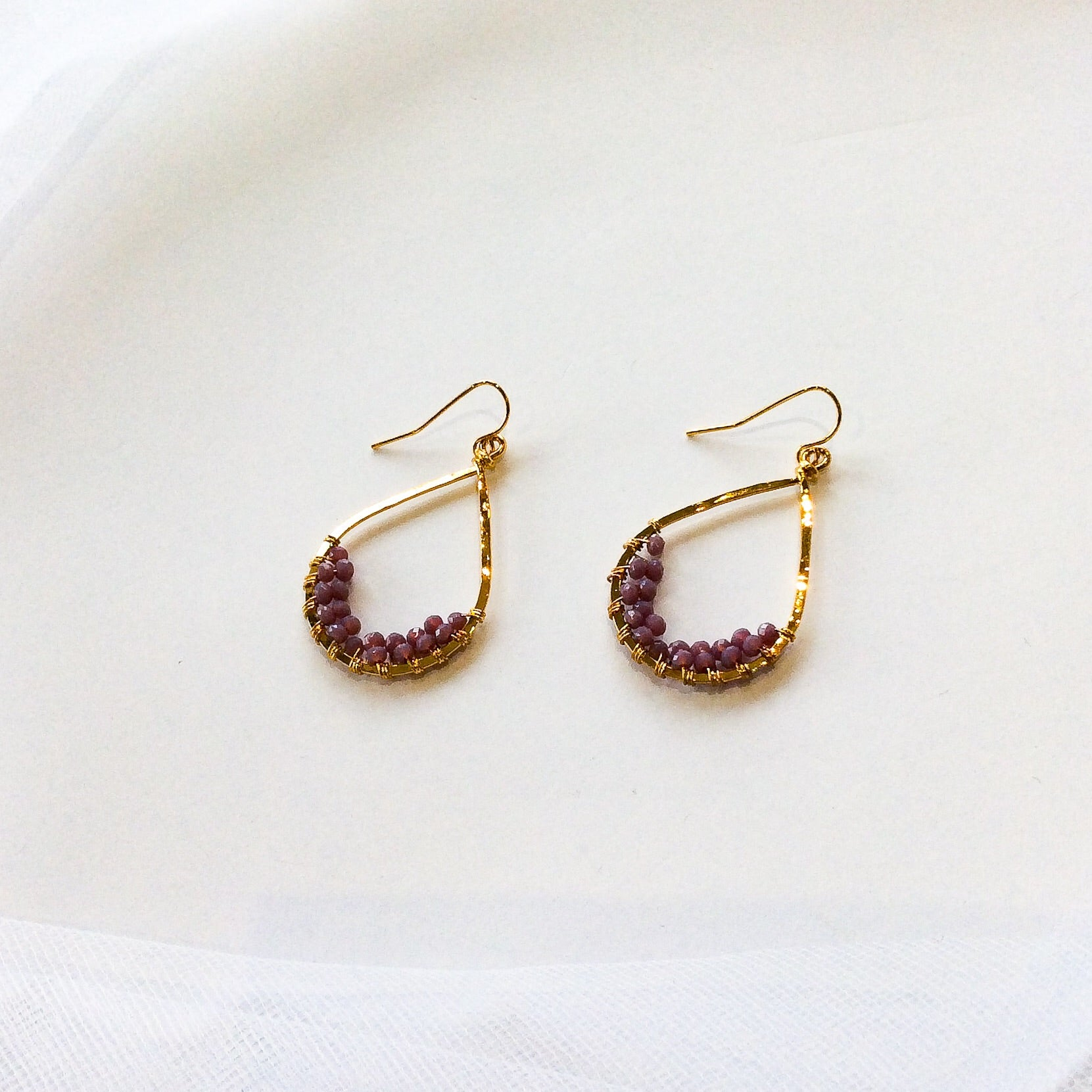 hammered gold plated tear drop earrings with light purple-pink beads wired onto the lower, inner half