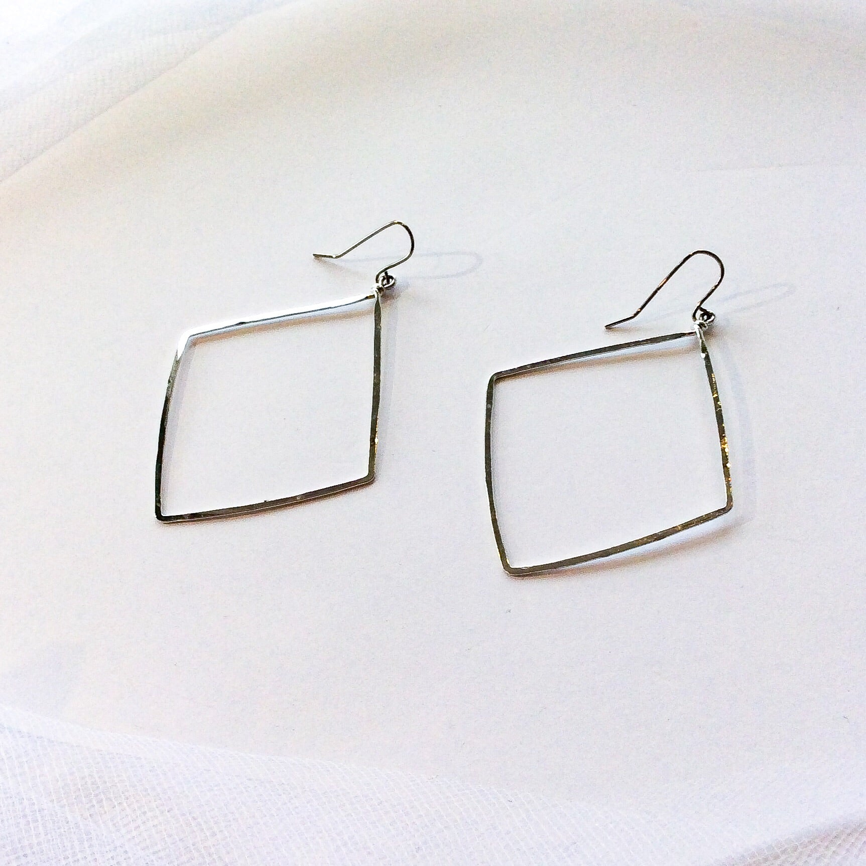 hammered, white gold plated earrings in the shape of a diamond