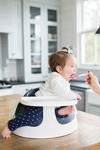 Baby sitting in her chair eating Square Baby pureed Baby Food - order online today!