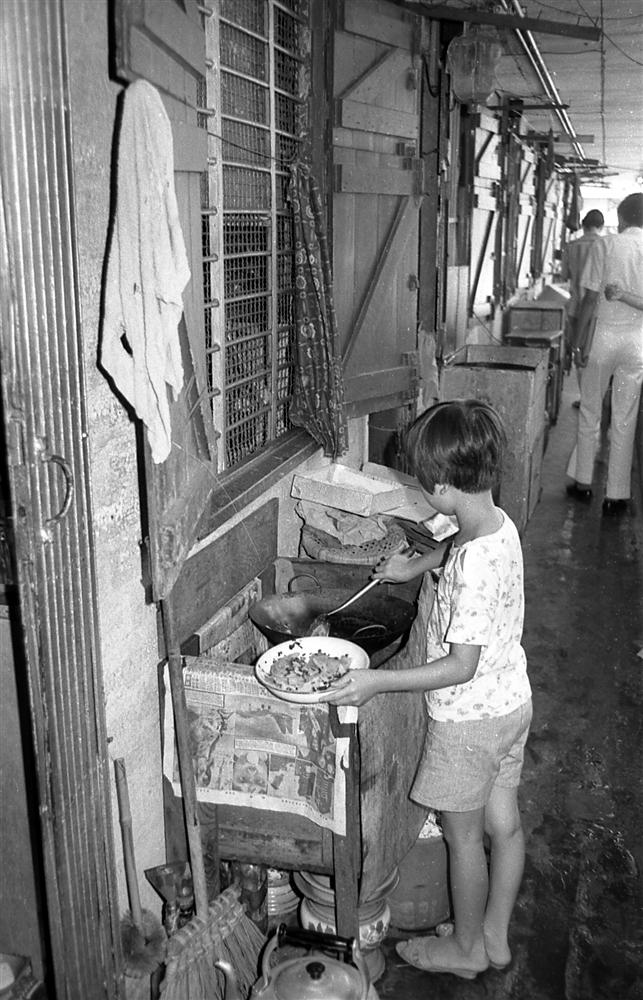 a young girl cooking with a wok in a corridor of a old Hong Kong Public Housing Estate