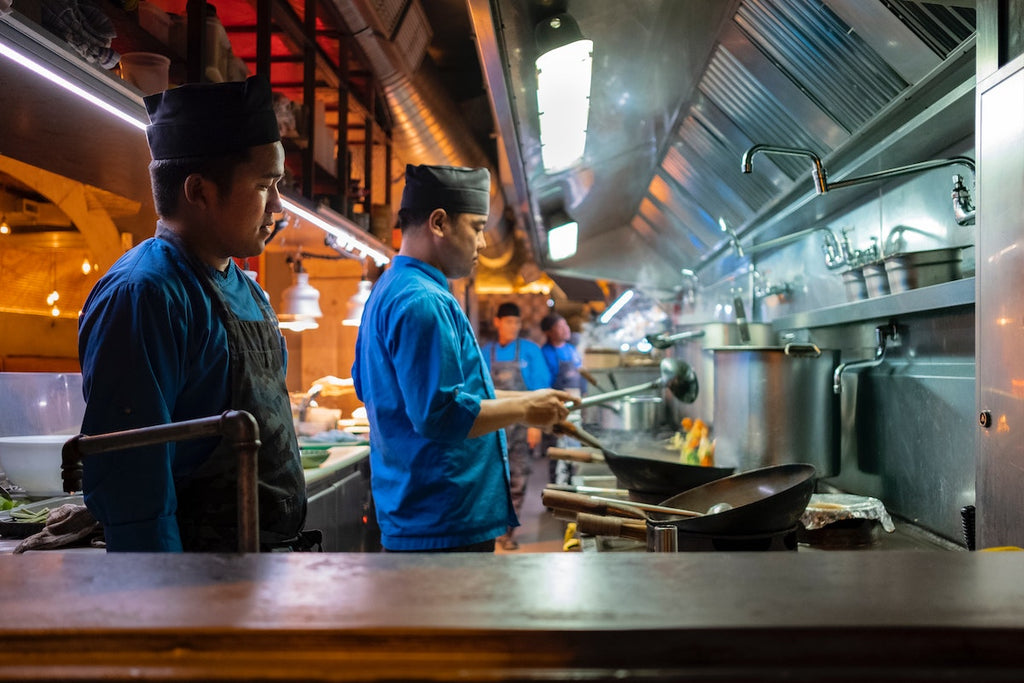 Chefs using multiple woks in a commercial kitchen