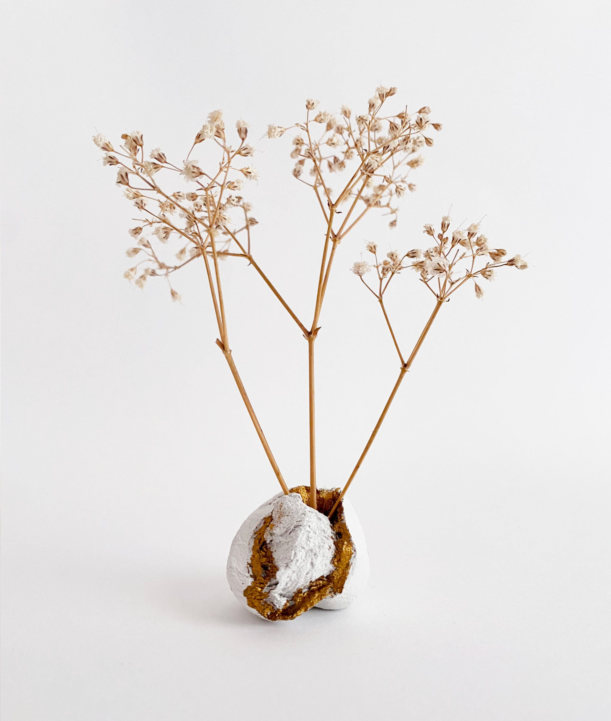 small sculpture made from dried flowers and clay with small touches of gold