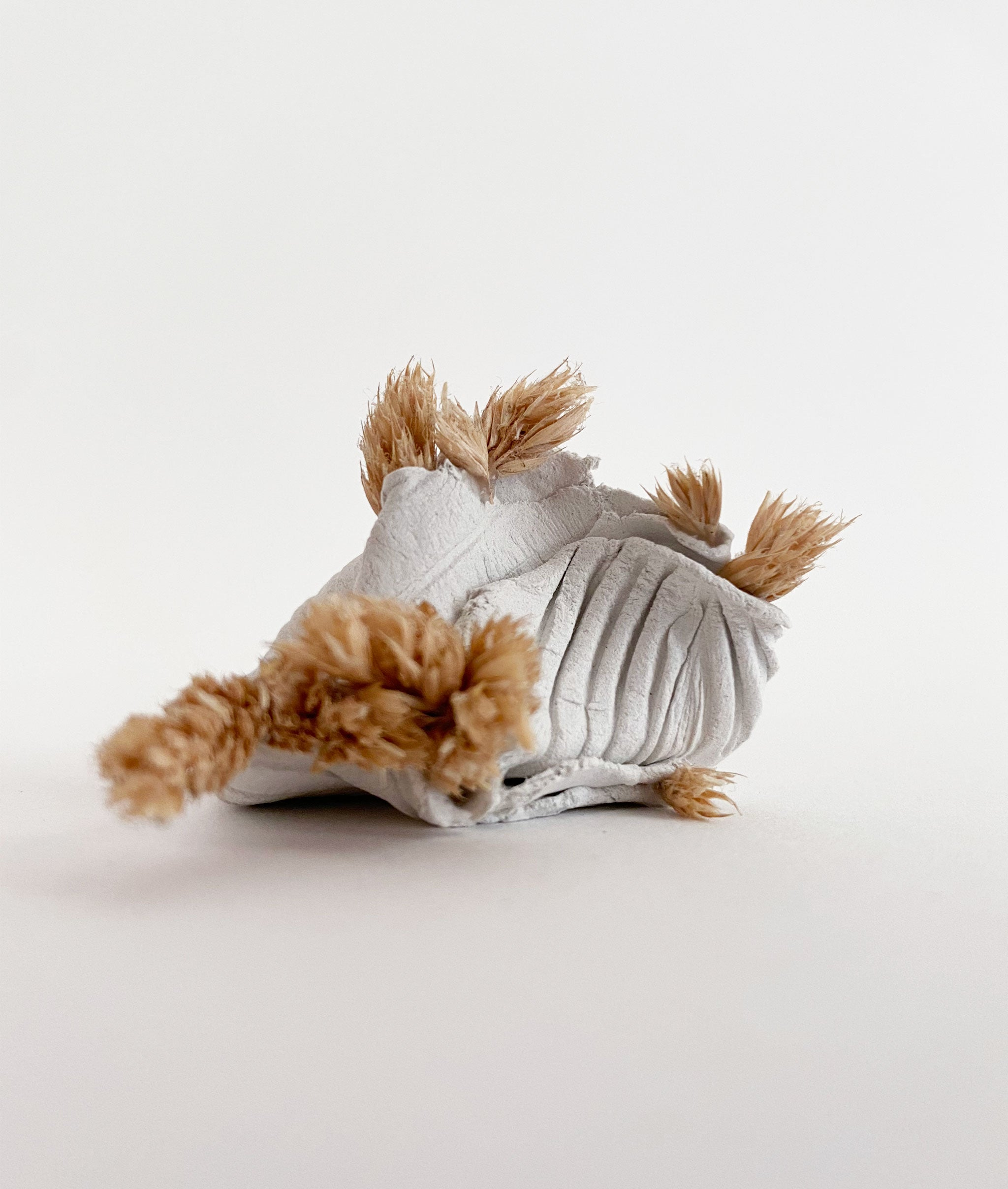 small sculpture created from dried foliage and clay