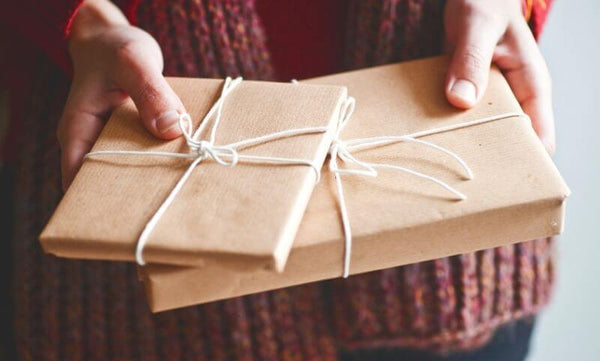 Hands holding two wrapped parcels that look like they contain chapter books