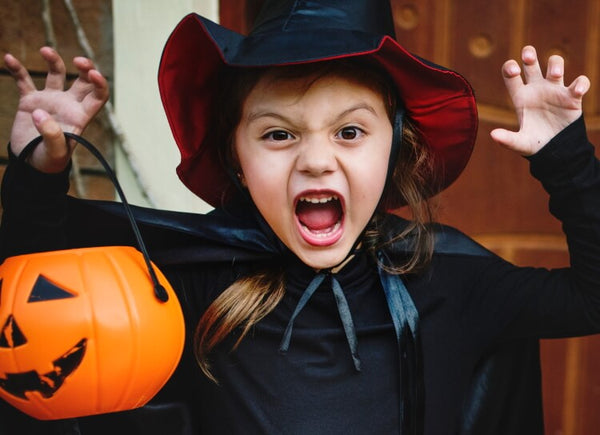Girl in witch costume holding a Halloween pumpkin basket