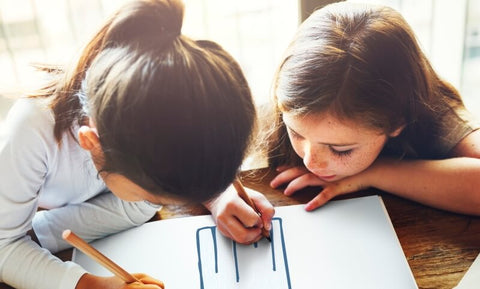 Two girls drawing together