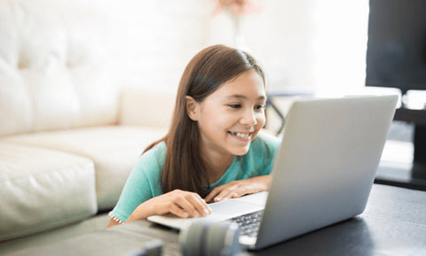 Girl smiling and looking at laptop