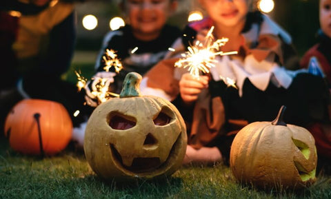Kids with pumpkins and sparklers having Halloween fun at home